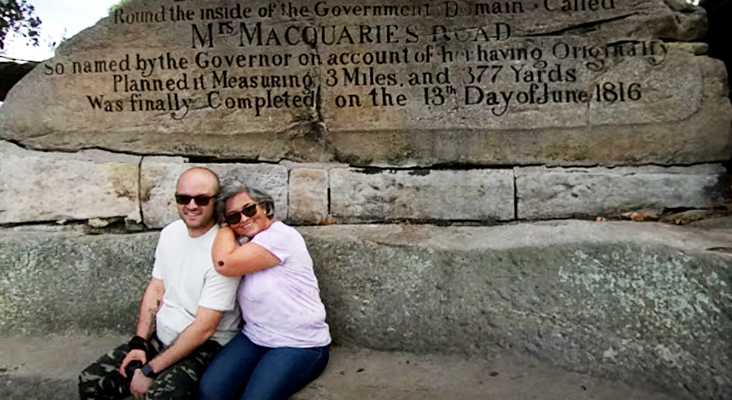 A couple sit on the historical Sydney Harbour landmark called Mrs Macquaries Chair